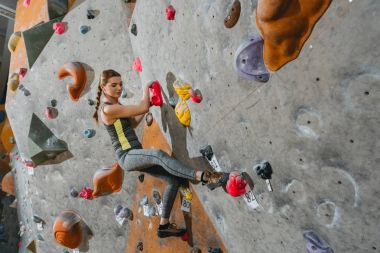 Full-length shot of young woman in sportive attire climbing a wall with grips at gym stock vector