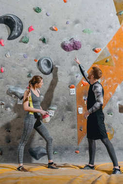 Full-length shot of young man pointing to grip on climbing wall and woman beside him looking at it stock vector