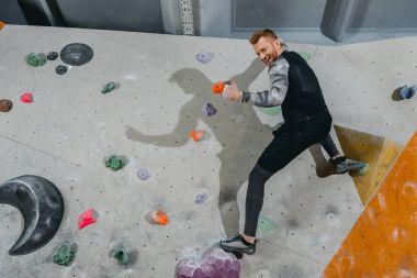 Man on climbing wall showing thumb-up