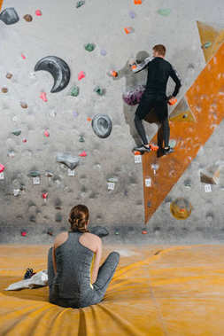Full-length shot of a young man in sportive attire climbing wall with grips and woman sitting on mat watching him stock vector
