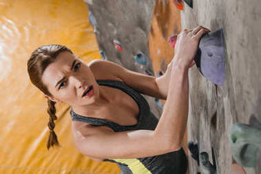 High-angle shot of young woman in sportive attire climbing a wall with grips at gym stock vector