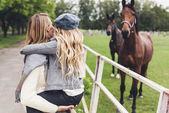 Fotografia madre e figlia al paddock con cavalli