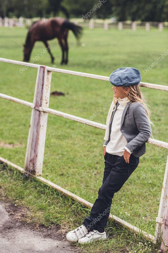 child at paddock with horse