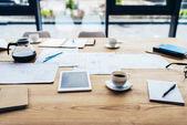 Digitální tablet s papíry a káva