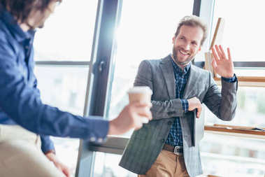 businessman waving hand to colleague