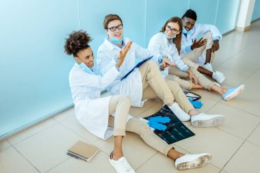 smiling doctors sitting in hospital corridor