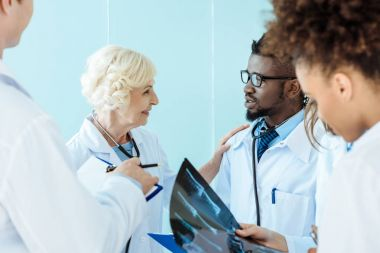 Senior doctor talking to african-american medical intern and touching him on shoulder stock vector