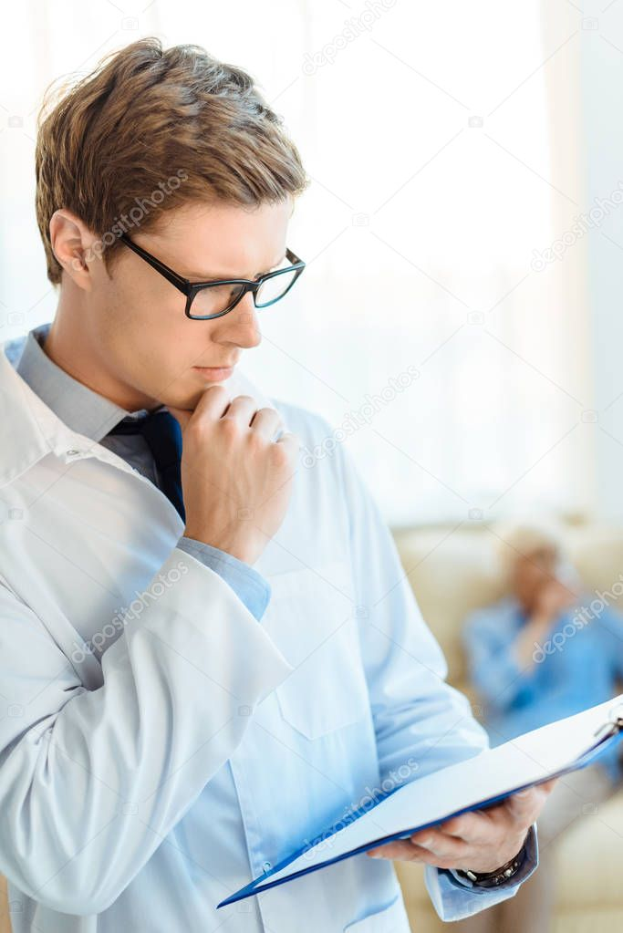 Doctor reading notes on clipboard