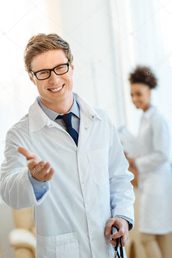 Smiling doctor holding out hand