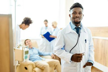Young african-american doctor in lab coat standing with his colleagues and male patient in the background stock vector