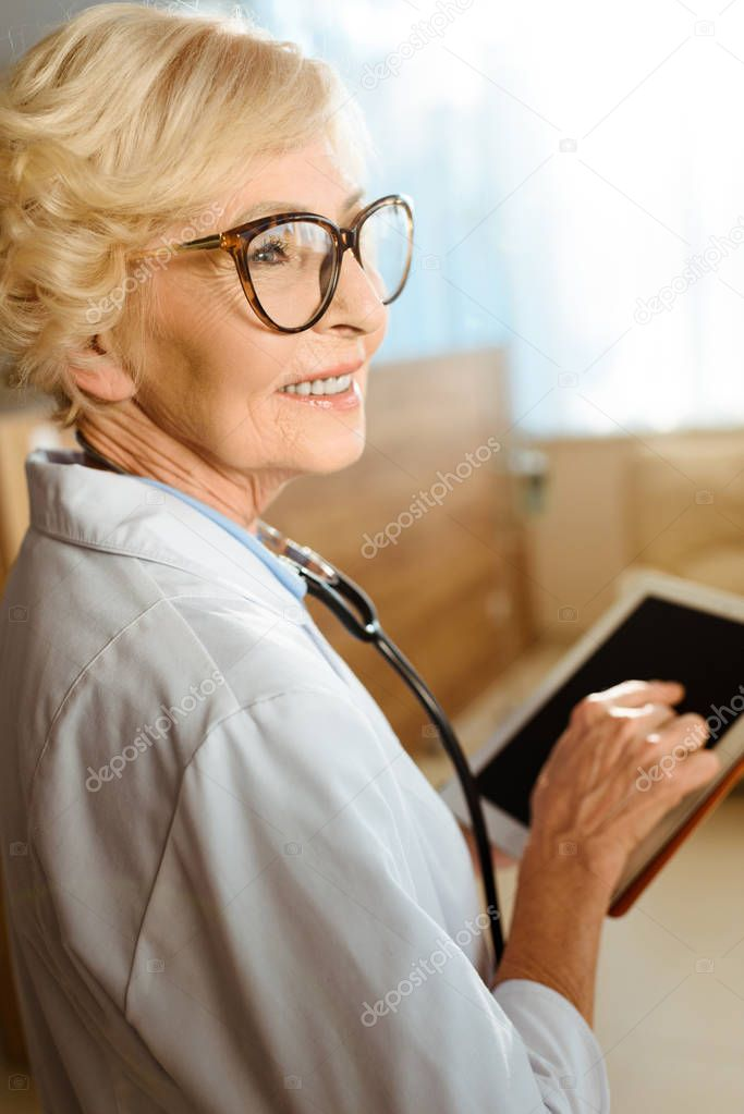 Senior doctor with digital tablet