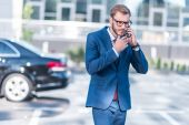 businessman with smartphone on parking