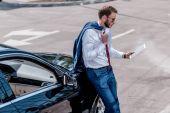Geschäftsmann mit Tablet am Auto