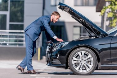 businessman in suit repairing car