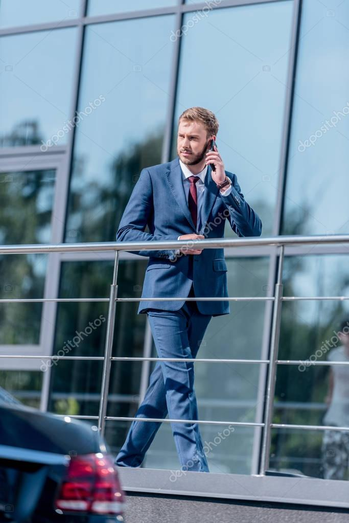 businessman with smartphone at office building