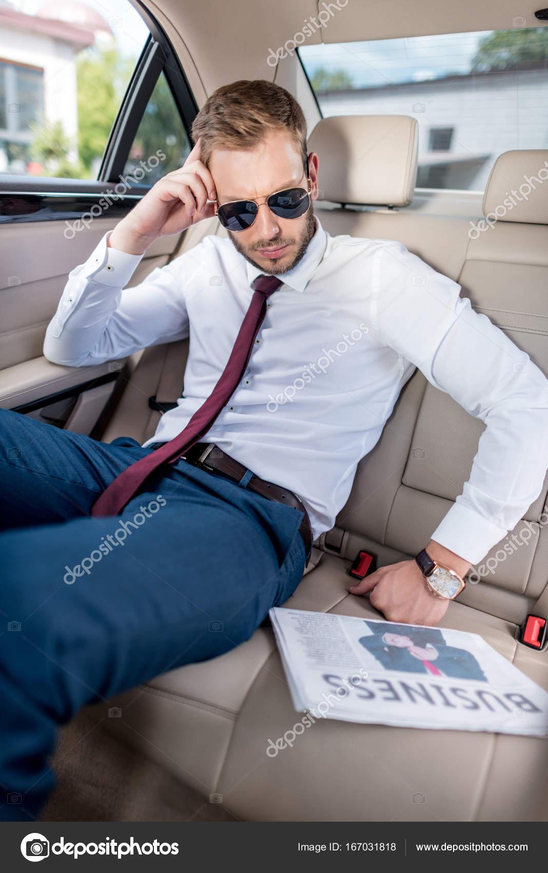 Молодий стильний бізнесмен в сонцезахисні окуляри з газеті «бізнес» на  сидінні автомобіля — Фото від ArturVerkhovetskiy c6478c85190ed