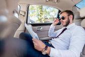 podnikatel s novinami v autě