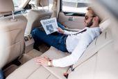 podnikatel s obchodní noviny na zadní sedadlo