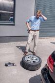 Fotografie muž měnící auto pneumatiky