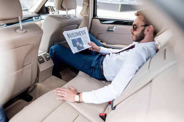 businessman with business newspaper on backseat