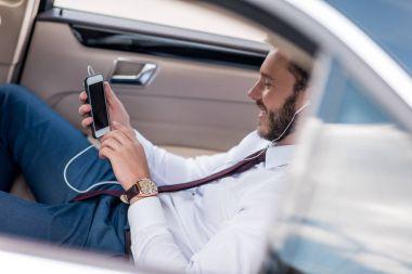 man listening music in car