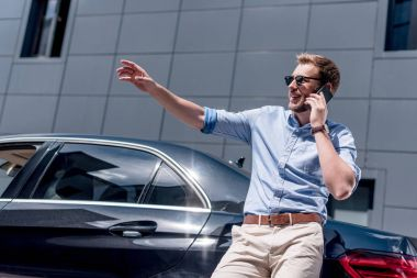 man with smartphone at car
