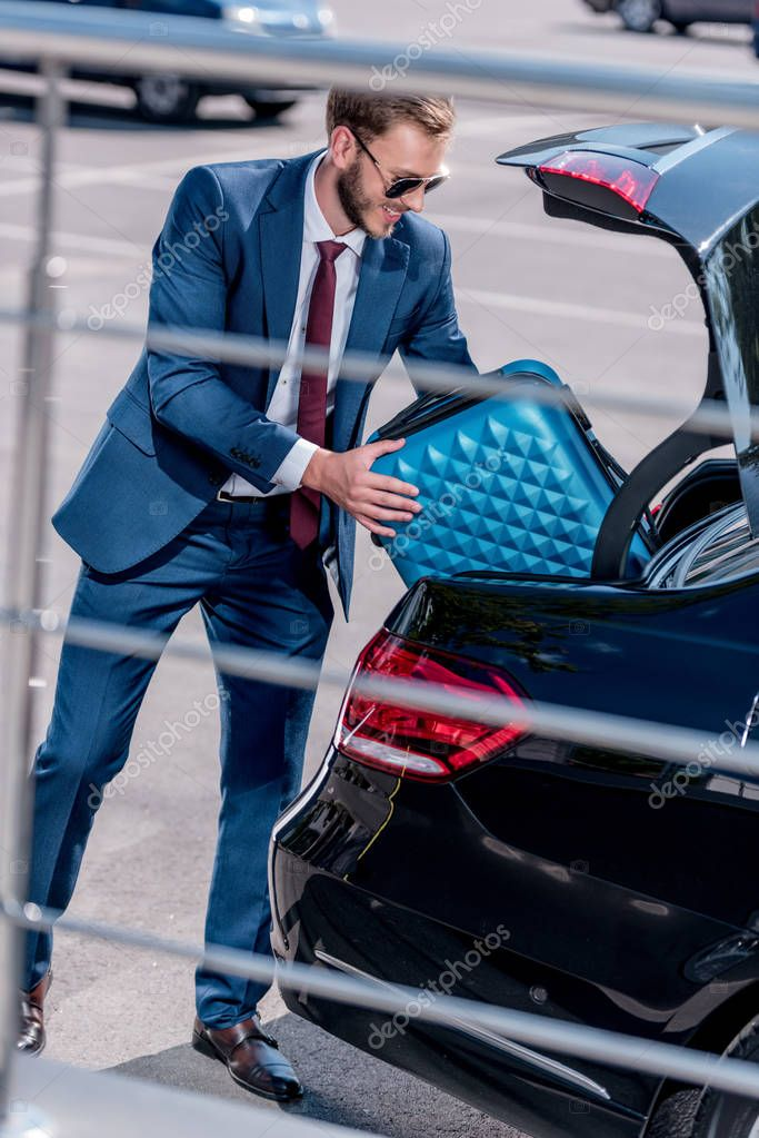 businessman with suitcase at car