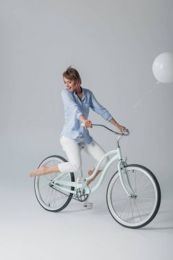 charming girl on bike with balloon