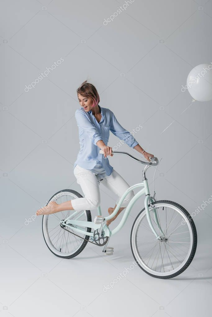 charming girl on bike with balloon