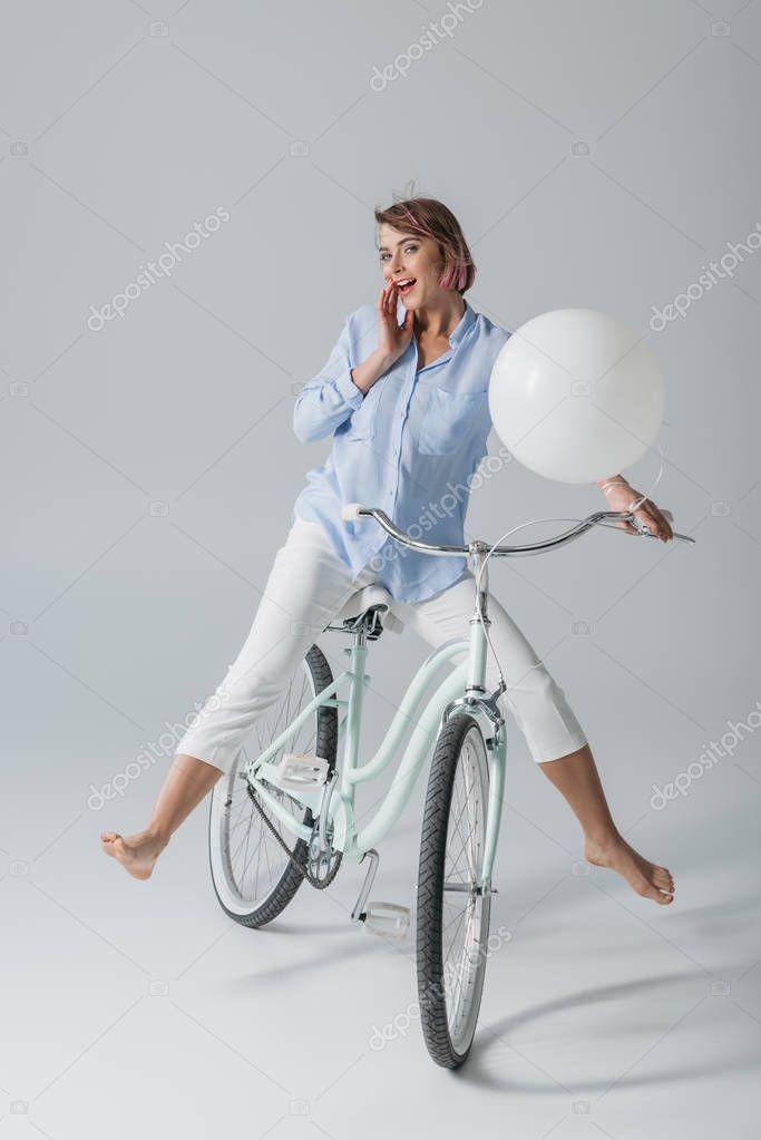 happy girl on bike with balloon