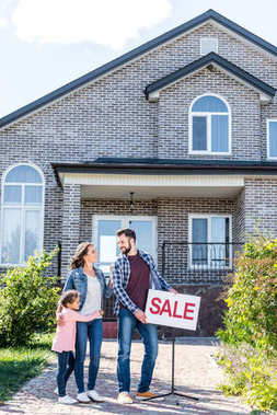 Family standing in front of house on sale