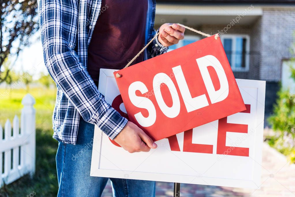 man hanging sold sign
