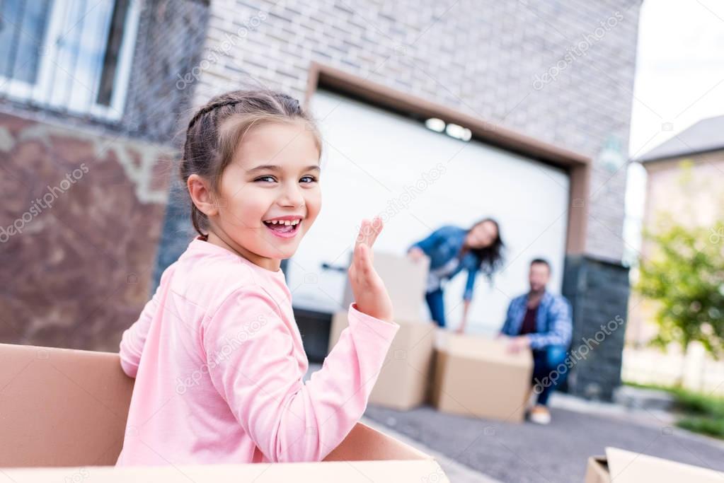 girl sitting in box and waving at camera