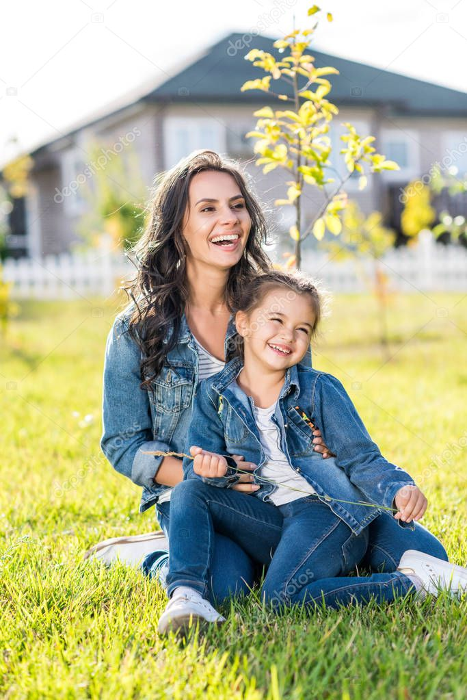 Mother and daughter sitting on grass