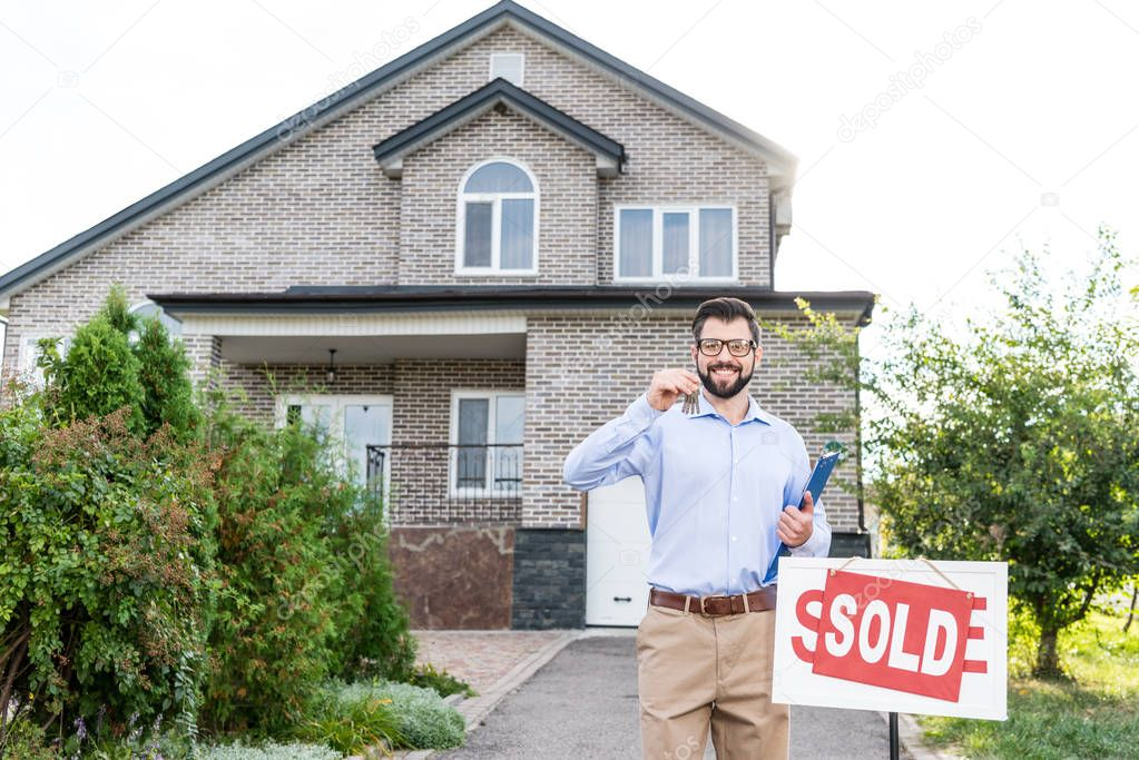 realtor with keys of sold house