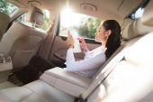 žena používající digitální tabletu v autě