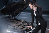 Fotografie woman looking under hood of car