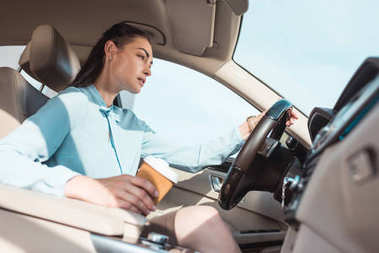 woman driving car with coffee