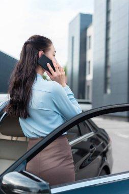 businesswoman talking on smartphone near car