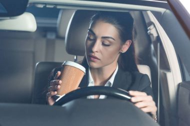 Woman driving and drinking coffee