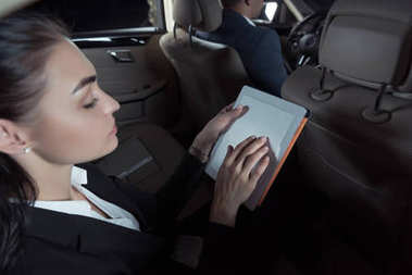 Woman in passenger seat using tablet