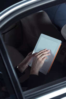woman using digital tablet in car