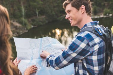 Handsome young hiker showing his girlfriend point on map stock vector