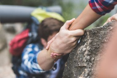 woman helping boyfriend to climb rock