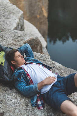 hiker relaxing on river shore