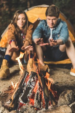 couple warming hands with bonfire