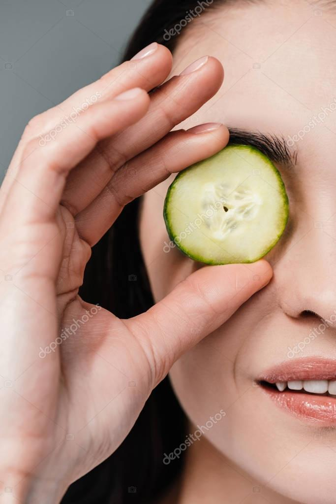Woman with slice of cucumber on eye