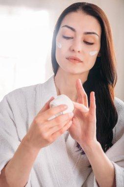woman in bathrobe applying face