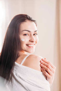 Smiling woman with cream applied to face