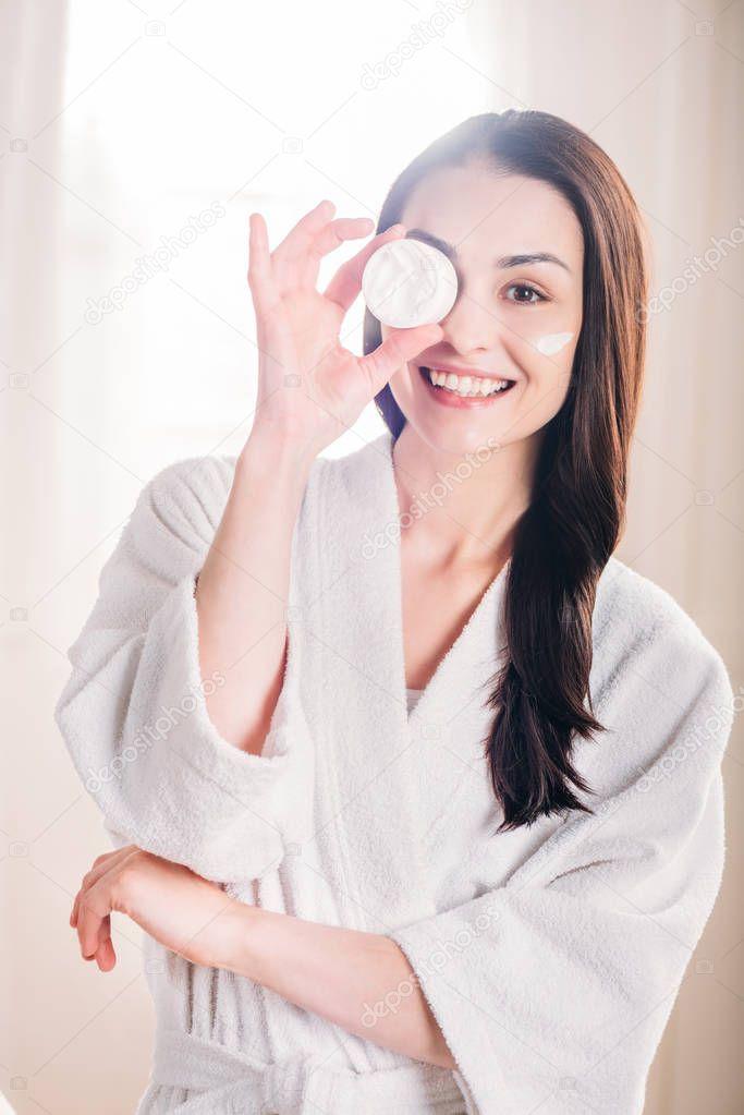Woman showing open jar of cream